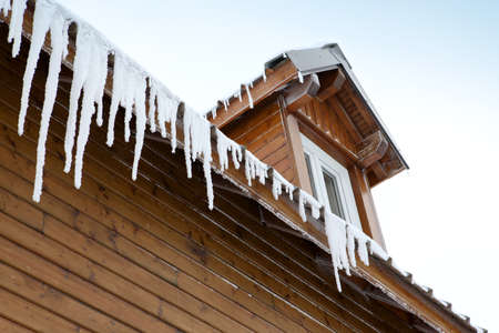 pointy: Icicles hanging from a roof edge Stock Photo