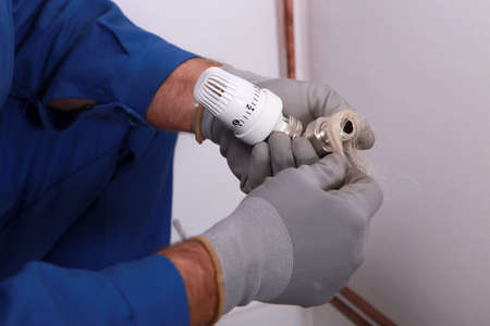 Plumber using hemp or similar fiber to waterproof a joint Foto de archivo