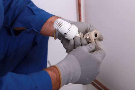 watertight: Plumber using hemp or similar fiber to waterproof a joint Stock Photo