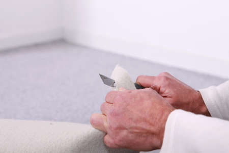 backing: Man cutting material with a utility knife Stock Photo
