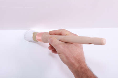 Closeup of a man cutting in a corner with white paint photo