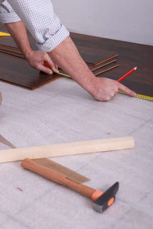 Man measuring laminate flooring photo