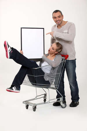 Playful couple with shopping trolley photo