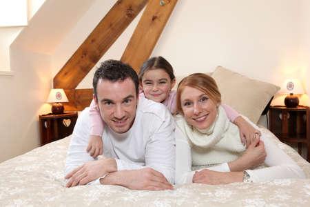 Padres e hija tendido en la cama photo