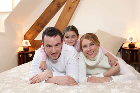 Parents and daughter laying on bed Stock Photo - 26102720