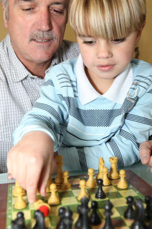 Senior man and grandson playing chess photo