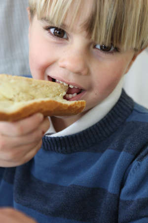 little blond boy eating slice of bread and butter photo
