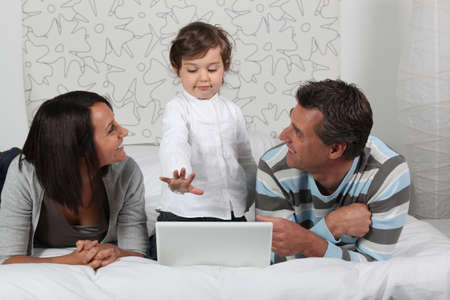 single father: Family on a bed with a laptop Stock Photo