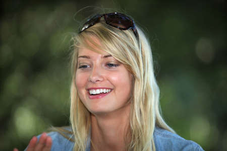 Blond woman wearing sunglasses on the top of her head photo
