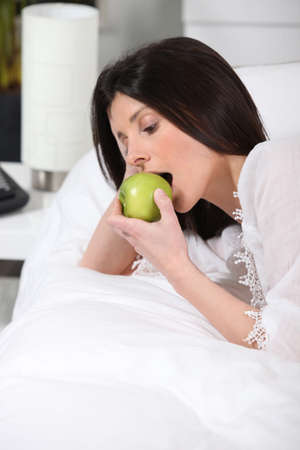 Woman eating an apple in bed photo