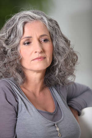 mature woman sitting on the couch photo