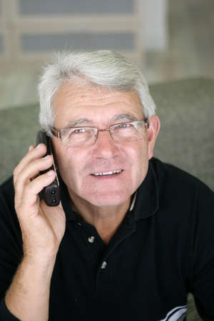 Senior man making a call from home photo