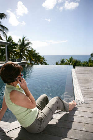 Senior woman making a call by the pool photo