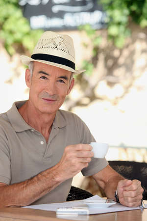 65 years old: 65 years old man wearing a straw hat and drinking a tea cup on a cafe terrace Stock Photo