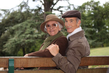 Elderly couple sat on bench photo