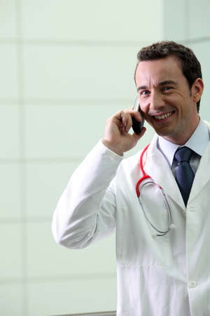 attired: Hospital doctor using a telephone