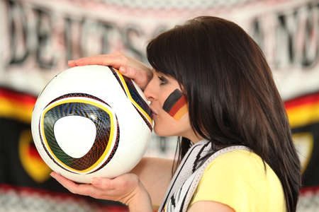 German fan kissing a football photo