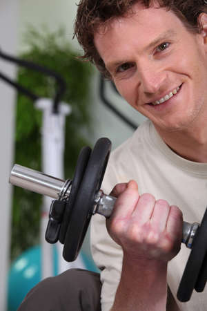 deltoids: Young man using weights in a gym