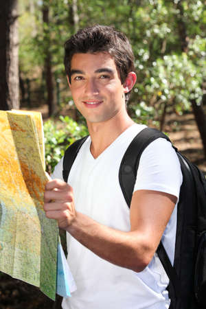 Young man reading a map in the forest photo