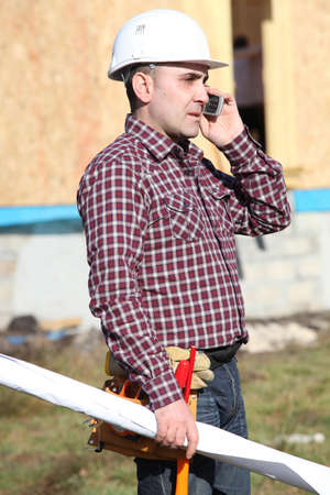 construction site supervisor talking on his cell photo