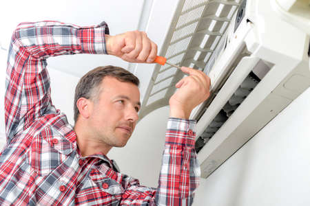 and the air: Man repairing air conditioning unit