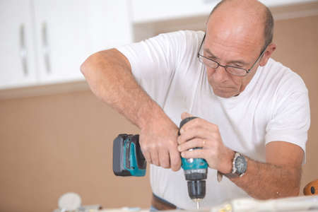 Carpenter drilling Into a wooden surface photo