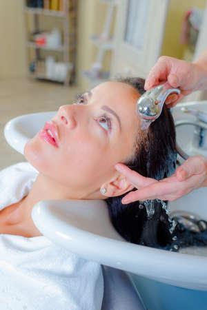 rubella: Hairdresser washing a woman Stock Photo
