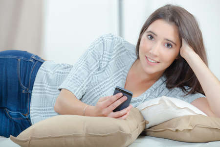 whilst: Sending a text message whilst laying on a sofa Stock Photo