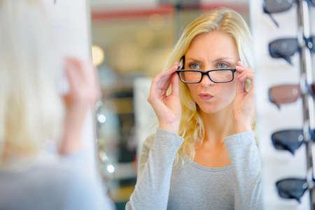 gafas: Mujer que intenta en gafas Algunas Foto de archivo