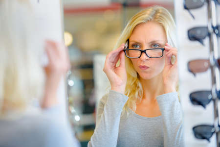 woman wearing glasses: Woman trying on glasses Some Stock Photo