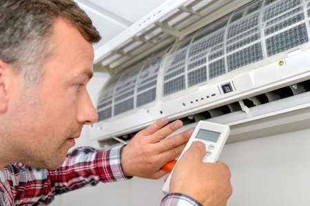'on the air': Man repairing air conditioning unit