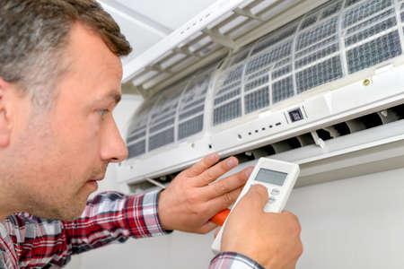 man in air: Man repairing air conditioning unit