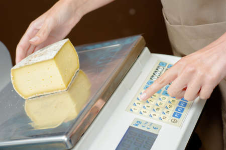 weighing: Woman weighing Some cheese