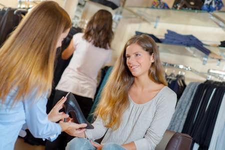 vistiendose: Asistente de ventas ayuda a la mujer pruebe un zapato