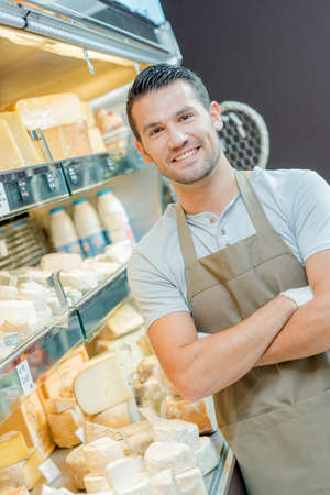 stocked: Male assistant at dairy counter