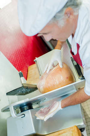 slicing: Butcher slicing ham Some for a customer