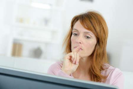 preocupacion: Tensionado mujer mirando la pantalla del ordenador Foto de archivo