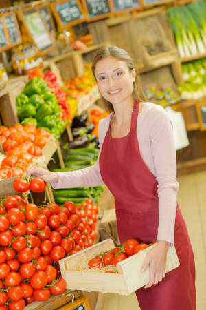 Shop worker carrying a crate of tomatoes Stock Photo