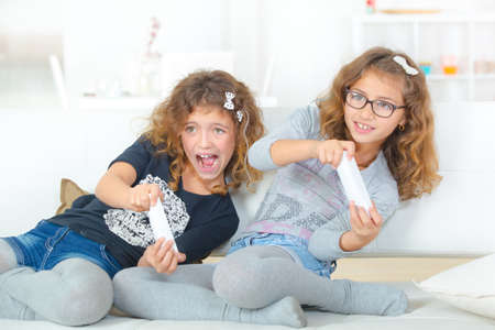 s video: Two young sisters playing video gales Stock Photo