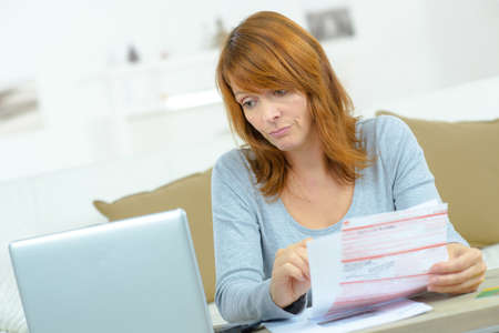 Woman with bills and computer photo