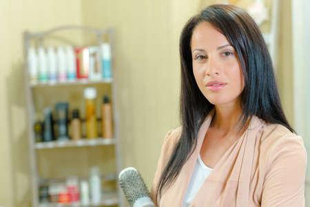stood: Hairdresser stood holding a brush