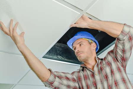 Peering onder een plafondpaneel