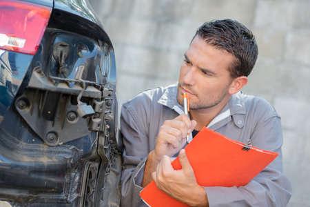assessing: Mechanic assessing a car