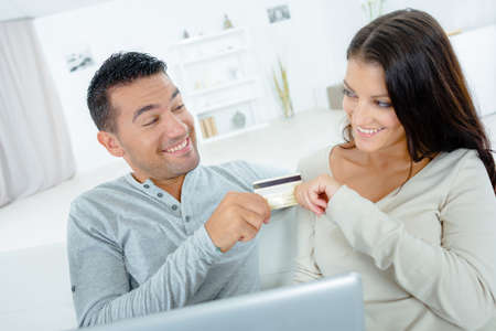 worries: Playful couple arguing over on-line shopping Stock Photo
