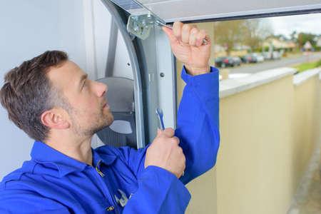 puerta de metal: Hombre que instala una puerta de garaje Foto de archivo