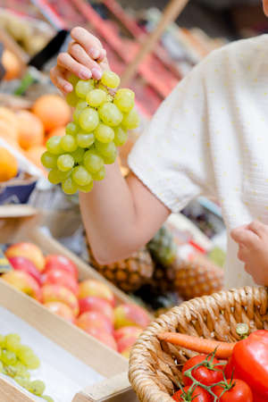 choose person: Woman choosing a bunch of grapes