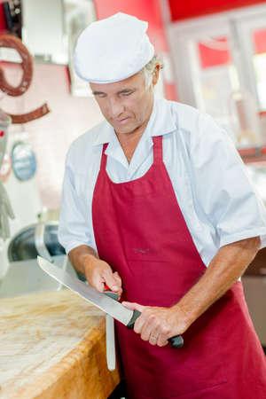 hone: Bucher sharpening Knife Stock Photo
