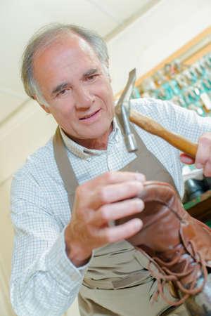 cobbler: Cobbler repairing shoes Stock Photo