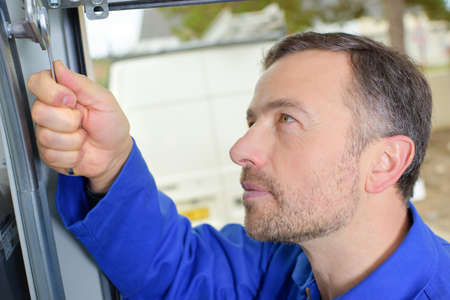 garage door: Man installing a garage door