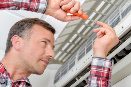 conditioner: Electrician fitting an air conditioning unit